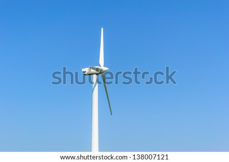 Wind turbine against blue sky. Wind power is the conversion of wind energy into a useful form of energy, such as using wind turbines to make electrical power.
