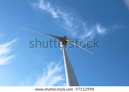 Wind turbine against clouds - stock photo