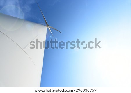 wind turbine against cloudy blue sky background. - stock photo