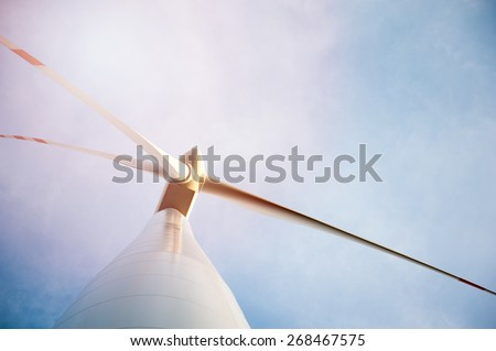 Wind turbine against deep blue sky - - stock photo