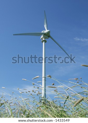 Wind turbine against deep blue sky with summer grasses in foreground