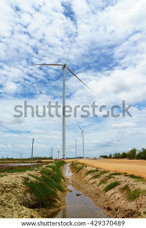 wind turbine against partly cloudy blue sky