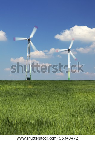 Wind turbine against the blue sky on the field