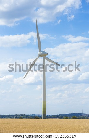 Wind turbine Alternative Energy with cloudy blue sky on a cornfield