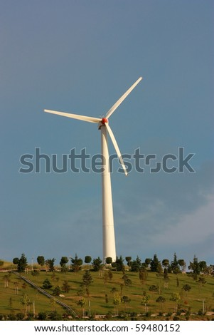 Wind turbine among trees in a park with blue sky - vertical - stock photo