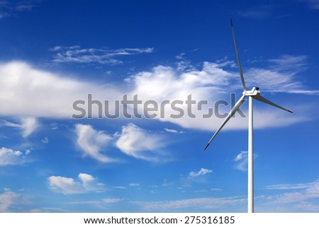 Wind turbine and blue sky with clouds at windy day - stock photo