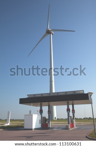 Wind turbine and gas station with a clear blue sky - stock photo