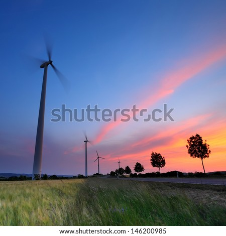 Wind turbine and wheat farm at sunset in Germany - stock photo