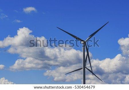 Wind turbine and white cloud in the blue sky.