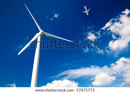 Wind turbine and white passenger airplane in the blue sky