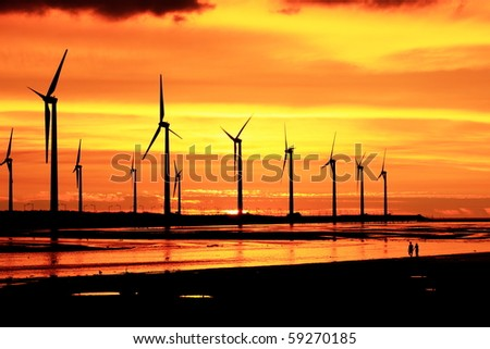 wind turbine array silhouette under sunset - stock photo