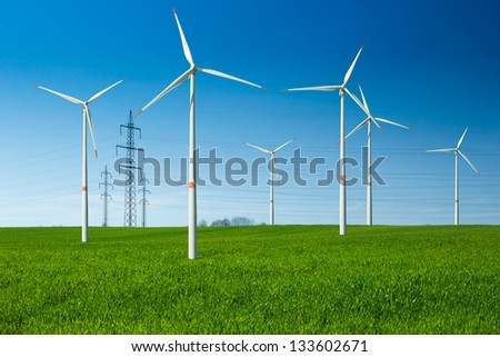 Wind turbine as renewable energy source, electricity pylon, wiring,  summer landscape with clear blue sky and green meadow - stock photo
