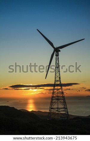 Wind turbine at sunset in an eolic park - stock photo