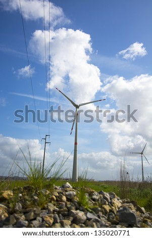 Wind turbine behind small mountain of rocks.