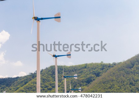 Wind turbine blue sky background agianst mountain, Clean energy