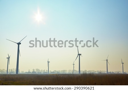 Wind turbine farm at morning time, image with copyspace - stock photo