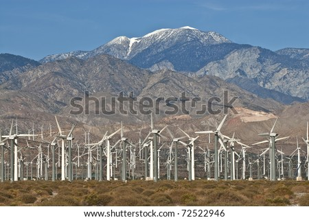 Wind Turbine farm located on California desert surrounded by mountains. - stock photo