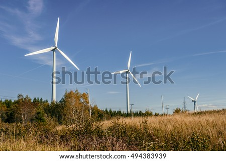 Wind turbine farm over blue sky at sunset
