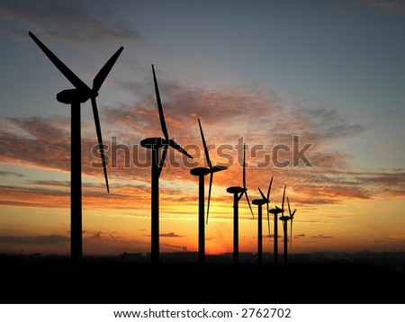 Wind turbine farm over sunset - stock photo