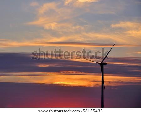 Wind turbine farm over sunset - stock photo