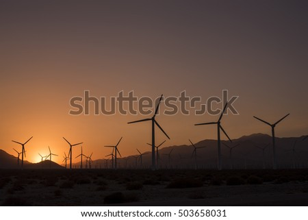 Wind turbine field at sunset with mountains