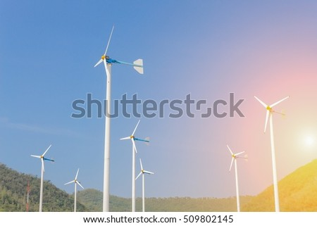 Wind Turbine for alternative energy, on background Sky and Mountain. with sunset light tone.