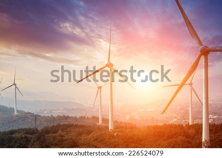 Wind Turbine from below with sun creating lens flare - stock photo
