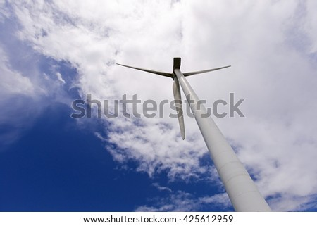 Wind turbine generating electricity, cloudy day - stock photo