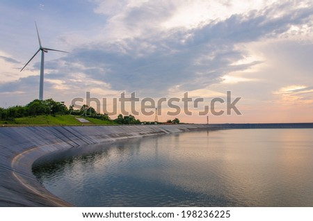 wind turbine generating electricity on dam catchment. - stock photo