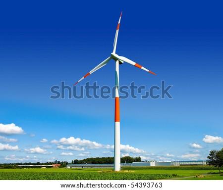 Wind turbine generating electricity on the beautiful green meadow. - stock photo