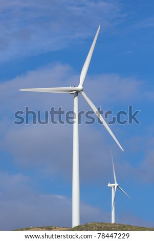 Wind turbine generating electricity with a nice white cloud on the sky - stock photo