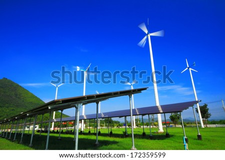 Wind turbine generator and solar energy panels with blue sky. - stock photo