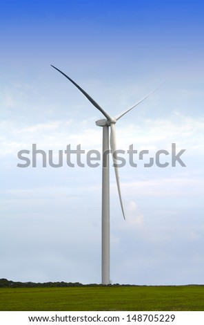 Wind turbine generator in a green meadow against a natural sky