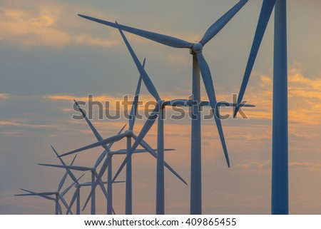 Wind turbine generator windmills backlit silhouetted in sunlight with clouds - stock photo
