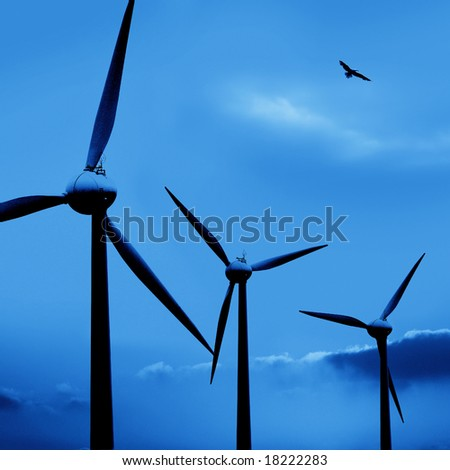 wind turbine in a row and a bird flying over blue sky
