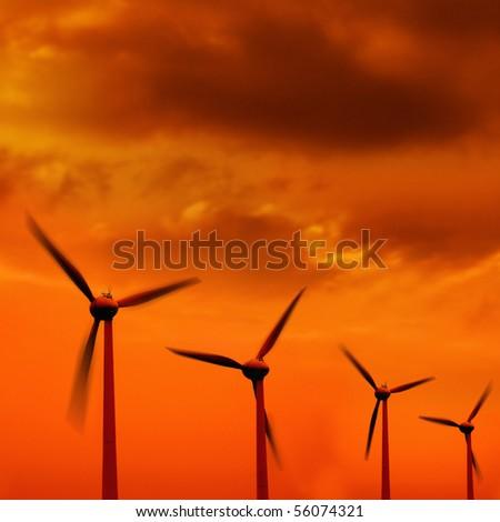 wind turbine in a row over orange background - stock photo