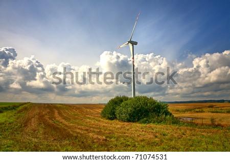 Wind turbine in an open field on cloudy day - stock photo