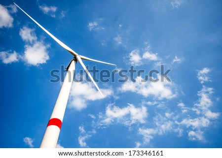 Wind turbine in daylight against bright blue sky