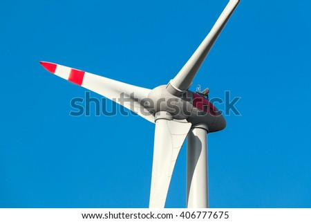 Wind turbine in front of blue cloudy sky