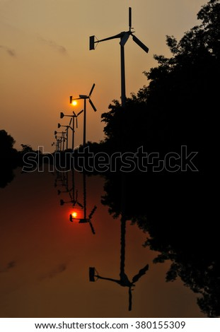 Wind turbine in morning with reflection in water - stock photo