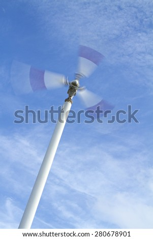 Wind turbine in on blue sky.