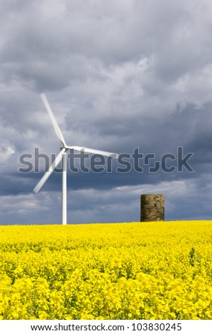 Wind turbine in rapeseed field with motion blur / Duel green energy from wind power and biofuel - stock photo