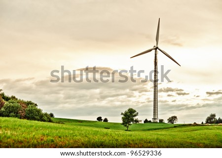 Wind Turbine in spring meadow at late afternoon - stock photo