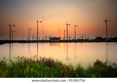 Wind turbine in sunset - stock photo
