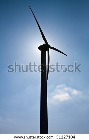 Wind turbine in the back light of the sun with blue sky and clouds