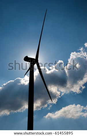 Wind turbine in the back light of the sun with blue sky and clouds.