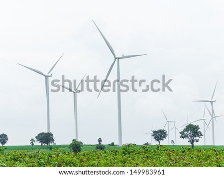 wind turbine in wind farm against cloudy sky - stock photo