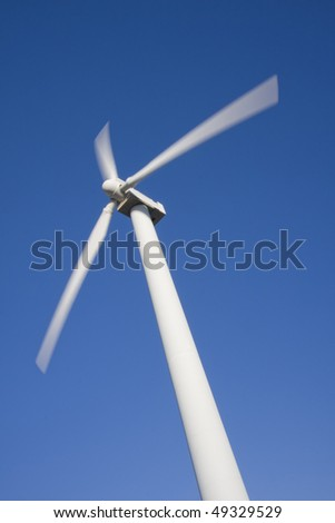 Wind turbine isolated over a blue sky. Alternative energy source - stock photo