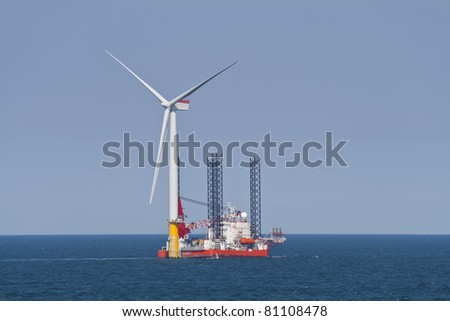 Wind turbine off the Norfolk Coast being constructed by a jack-up vessel - stock photo