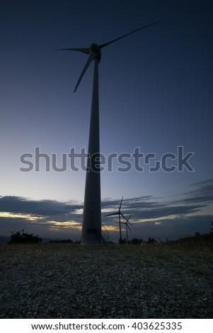 wind turbine on a hill at sunset with clouds behind